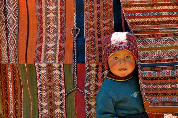 Peru CTTC Weavers Peeking Between Textiles
